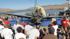 Folks gather around a SB2C Helldiver after it was recovered from 91 feet down and under six or seven feet of organic silt in a San Diego reservoir, Friday, Aug. 20, 2010. (AP / Chris Carlson)