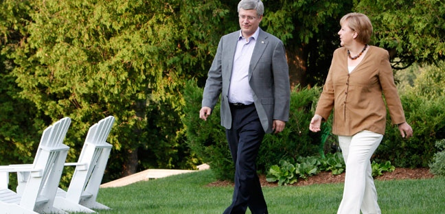 Prime Minister Stephen Harper chats with German Chancellor Angela Merkel at the Prime Minister's official country residence at Harrington Lake, Quebec, Wednesday Aug.15, 2012. (Fred Chartrand / THE CANADIAN PRESS)