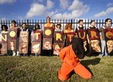 A demonstrator dressed in an orange jumpsuit kneels on the ground in front of a group of protesters carrying art signs that spell 'No Torture' outside the Pentagon's U.S. Southern Command in Doral, Fla., Friday, Jan. 11, 2008. (AP /Miami Herald, Ricardo Lopez)