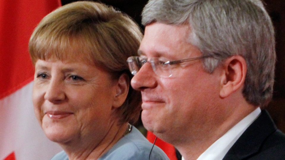 Prime Minster Stephen Harper and German Chancellor Angela Merkel share a moment during a joint news conference on Parliament Hill, in Ottawa, Thursday Aug. 16, 2012. (Fred Chartrand / THE CANADIAN PRESS)