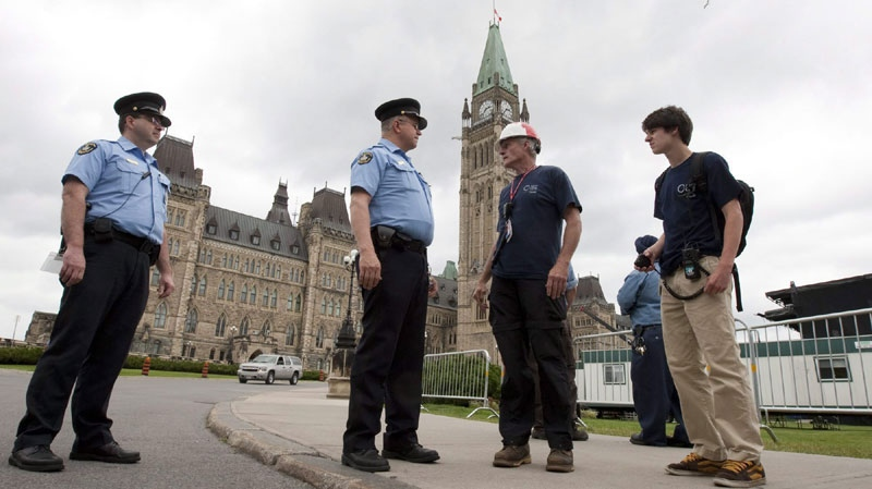 Parliamentary security guards stop construction workers from returning to their work site after Parliament buildings were evacuated following an earthquake in Ottawa, Wednesday June 23, 2010. (THE CANADIAN PRESS/Adrian Wyld)