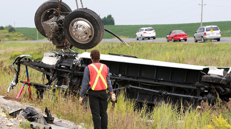 The front wheels of a coach bus that were sheared off in an accident are lifted from the debris at the scene of the crash on Highway 401 in Woodstock, Ontario, Sunday, August 22, 2010. (Dave Chidley / THE CANADIAN PRESS)