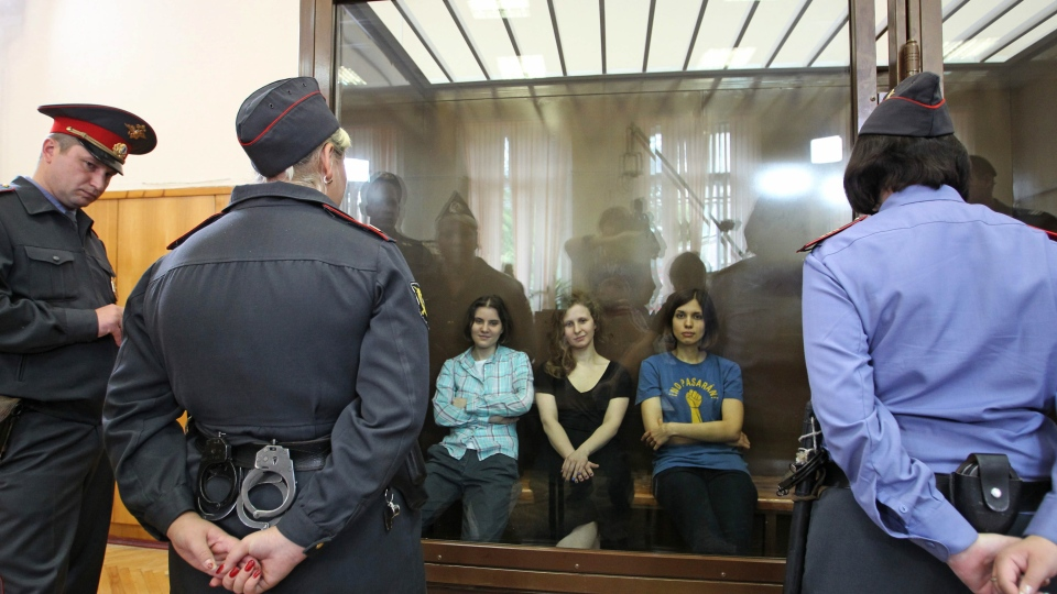 Feminist punk group Pussy Riot members, from left, Yekaterina Samutsevich, Maria Alekhina and Nadezhda Tolokonnikova sit in a glass cage at a court room in Moscow, Russia on Friday, Aug 17, 2012.  (AP / Mikhail Metzel)