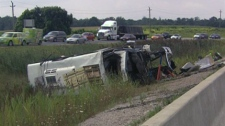 A bus lays on its side after it crashed in the eastbound lanes of Highway 401, near the junction with Highway 403 on Sunday, Aug. 22, 2010.
