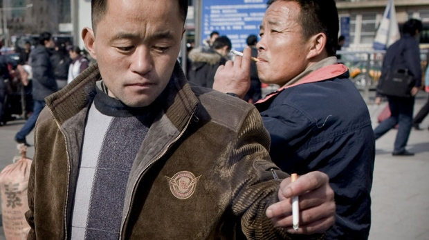 Chinese men smoke cigarettes outside a train station in Beijing, China, Monday, Feb. 16, 2009. (AP / Andy Wong)