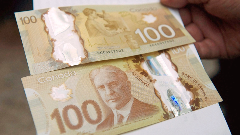 The Bank of Canada's new circulating $100 bill, Canada's first polymer bank note, is shown in Toronto on Monday Nov. 14, 2011. (Nathan Denette / THE CANADIAN PRESS)