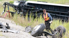 A tow truck operator looks at the front wheels that were sheared off, in the debris in at the scene of a coach bus accident on Highway 401 in Woodstock, Ontario, Sunday, August 22, 2010. (Dave Chidley / THE CANADIAN PRESS)
