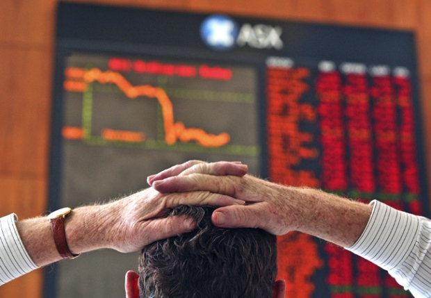 A lunch time visitor to the Australian Securities Exchange watches a board showing stock prices and a graph of the day's trade in Sydney, Australia on Wednesday, Jan. 16, 2008. (AP / John Pryke)