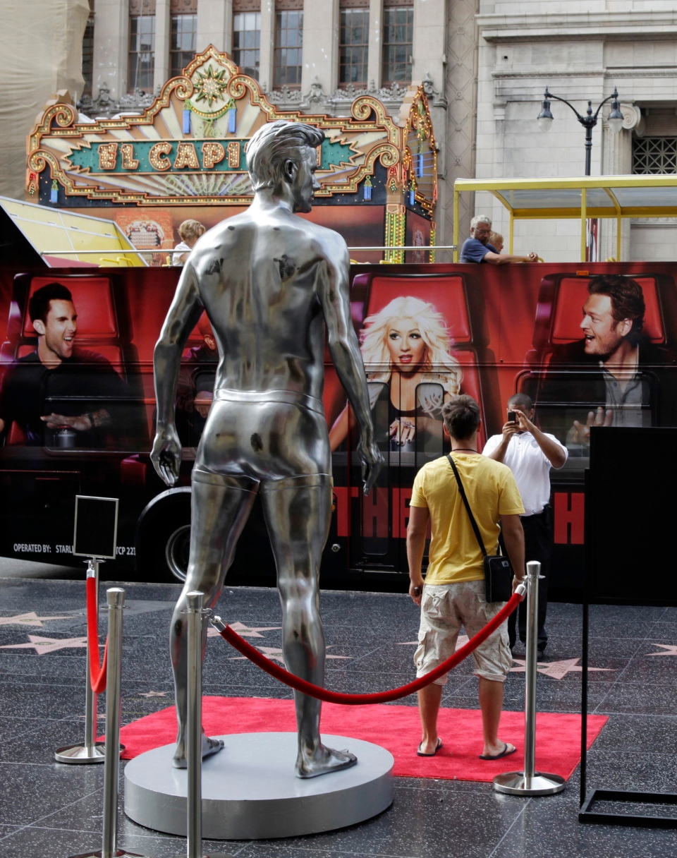 A statue of English soccer player David Beckham is photographed by tourists in the Hollywood section of Los Angeles Friday, Aug. 17, 2012. (AP /Damian Dovarganes)