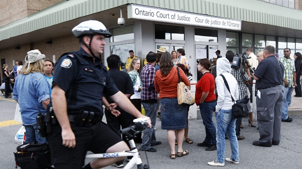 Members of the media and police gather around people scheduled to make their court appearances charged with various offences stemming from the G20 summit in Toronto on Monday, Aug. 23, 2010. (Nathan Denette / THE CANADIAN PRESS)