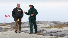 Prime Minister Stephen Harper, left, is given a tour of the Cape Merry Historical Site by heritage presenter for Parks Canada Leroy O'Higgins in Churchill, Manitoba, on the first day of his five day northern tour on Monday Aug. 23, 2010. (Sean Kilpatrick / THE CANADIAN PRESS)