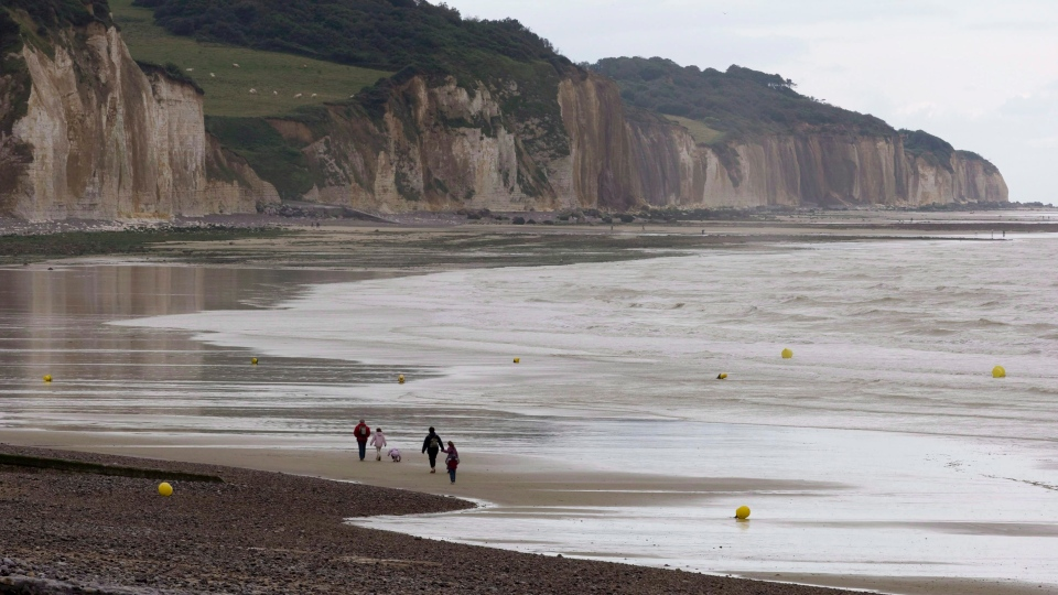 A family walks the shore of Pourville, France, Monday, August 20, 2007. (CP / Paul Chiasson)