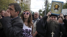 A man, right, who appears to be an Orthodox priest among protesters in Moscow on Aug. 17, 2012.