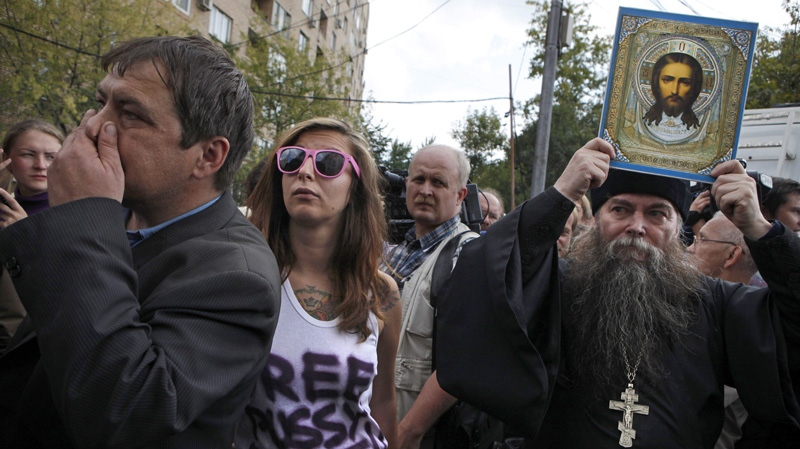 A supporter of the Russian punk group Pussy Riot, second left, and a man, right, who appears to be an Orthodox priest, a Pussy Riot opponent, stand outside a court in Moscow, Russia, Friday, Aug. 17, 2012. (AP Photo/Alexander Zemlianichenko)