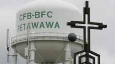 A cross on top of St. Francis of Assisi Church is seen in front of a water tower at CFB Petawawa, Monday, Sept. 4, 2006. (Jonathan Hayward / THE CANADIAN PRESS)