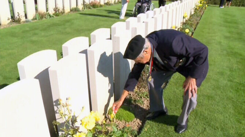 A veteran stoops to place a flag on the grave of a soldier in a cemetery near Dieppe, France, Aug. 18, 2012.