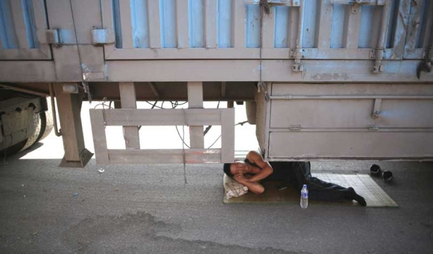 In this photo taken Monday, Aug. 23, 2010, a driver takes a nap under his truck jammed on an entrance ramp to the Beijing-Tibet Highway in Guoleizhuang township, in north China's Hebei province. The massive traffic jam that stretches for dozens of miles hit its 10-day mark on Tuesday.(AP Photo)