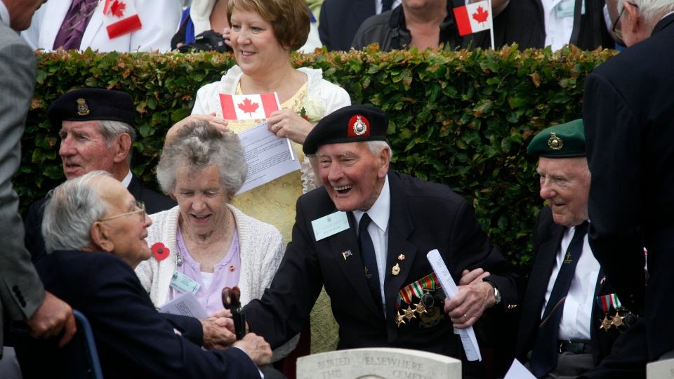 Dieppe veteran Bill Valentine, centre, smiles during the commemorations to honour allied soldiers killed 70 years ago in a failed World War II invasion, which take place at the Cemetery of Virtues in Dieppe, northern France on Sunday, Aug. 19, 2012.  (AP / Michel Spingler)