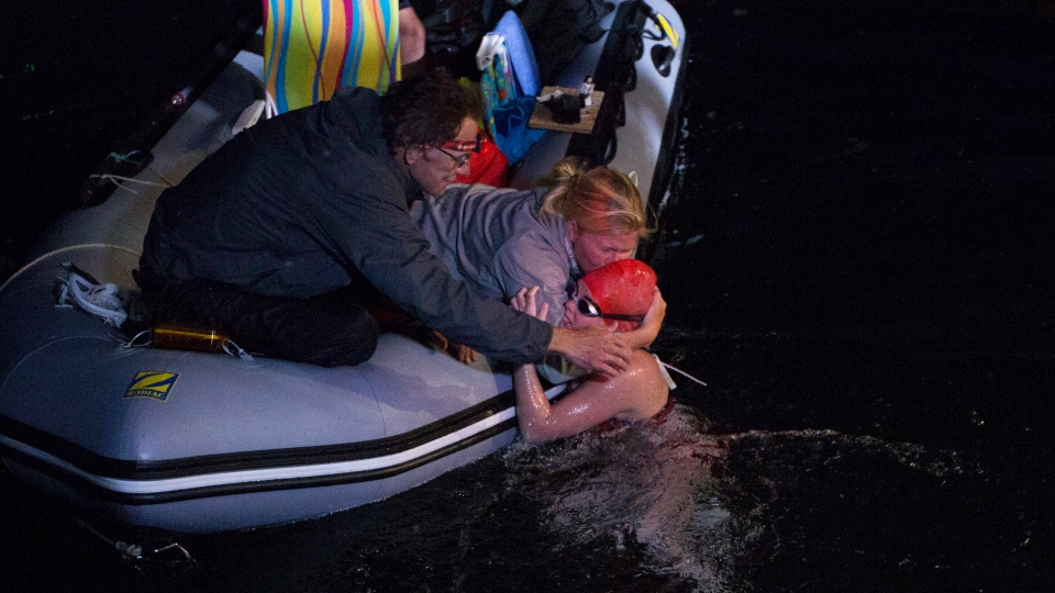Annaleise Carr is embraced after she officially finished her record breaking overnight Lake Ontario swim from Niagara-on-the-lake to Toronto on Sunday August 19, 2012. (Michelle Siu / THE CANADIAN PRESS)