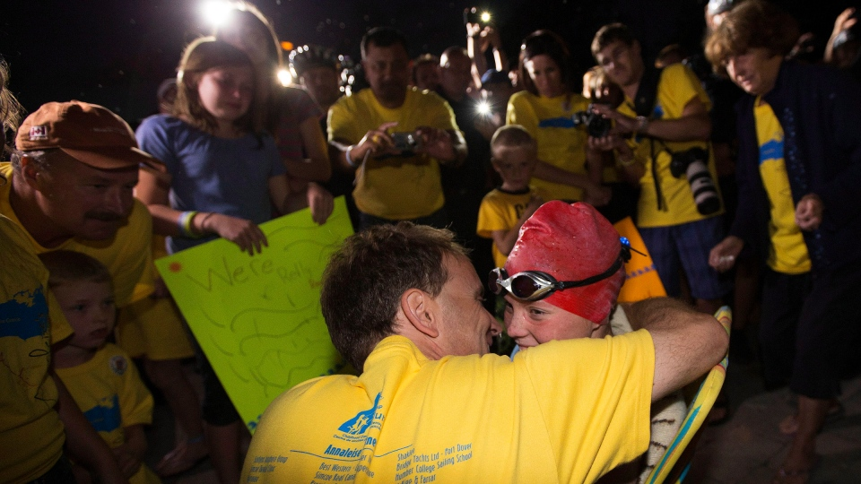 Annaleise Carr is surrounded by supporters as she finishes a record breaking overnight Lake Ontario swim from Niagara-on-the-Lake to Toronto on Sunday August 19, 2012. (Michelle Siu / THE CANADIAN PRESS)