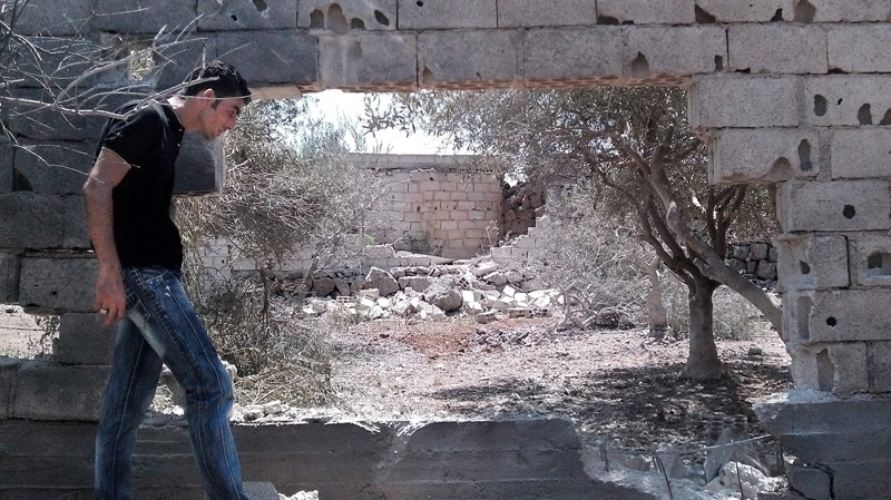 In this citizen journalism image provided by Shaam News Network SNN, taken on Sunday, Aug. 12, 2012, a Syrian man walks past a damaged wall from shelling in Daraa, Syria. (AP Photo/Shaam News Network, SNN)
