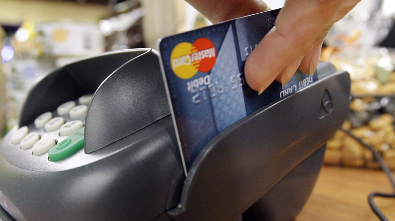 A customer swipes a debit card in this Nov. 2, 2009 file photo. (AP Photo/Elaine Thompson, file)