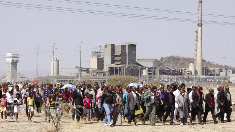 A group of churchgoers proceed to a memorial service near the Lonmin platinum mine near Rustenburg, South Africa on Sunday Aug. 19, 2012. (AP Photo/Denis Farrell)