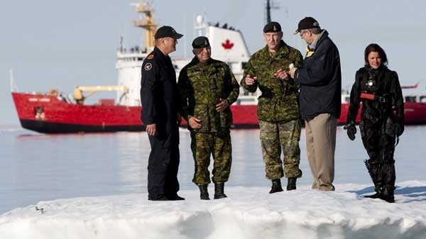 Prime Minister Stephen Harper, second from right, stands on an iceberg as he talks with Chief of the Defence Staff General Walter Natynczyk (centre) as they take part in a training exercise during Operation Nanook in Resolute, Nunavut on the third day of his five-day northern tour to Canada's Arctic on Wednesday Aug. 25, 2010. (Sean Kilpatrick / THE CANADIAN PRESS)