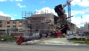 A collapsed crane lies on it's side after an incident at a west-end Toronto construction