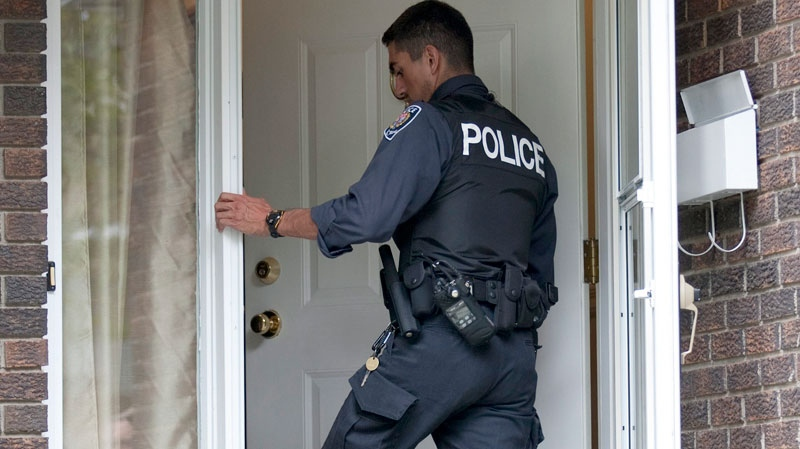 A police officer stands in the doorway to a house raided earlier in the day in the west end of Ottawa, Wednesday August 25, 2010. (Adrian Wyld / THE CANADIAN PRESS)