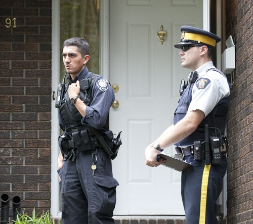 Ottawa and RCMP police officers stand guard outside a home raided earlier in the day in the west end of Ottawa, Wednesday, Aug. 25, 2010. (Adrian Wyld / THE CANADIAN PRESS)