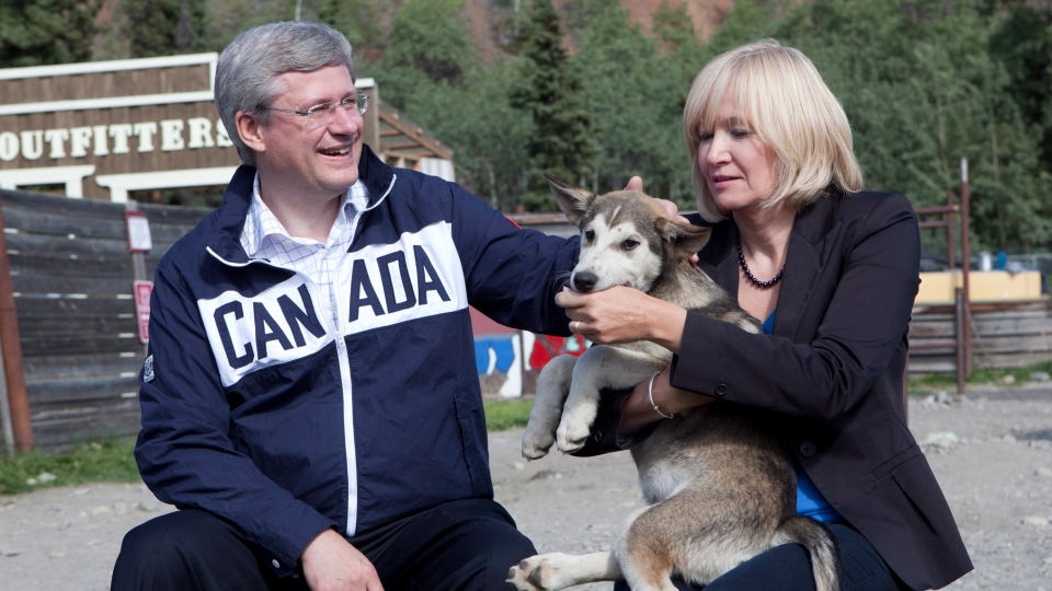 Prime Minister Stephen Harper and his wife Laureen pet a husky dog as they tour Caribou Crossing, Yukon, south of Whitehorse Monday Aug. 20, 2012. (Adrian Wyld / THE CANADIAN PRESS)