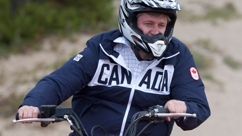 Prime Minister Stephen Harper rides an all terrain vehicle around sand dunes near Caribou Crossing, Monday, Aug. 20, 2012. (Adrian Wyld / THE CANADIAN PRESS)