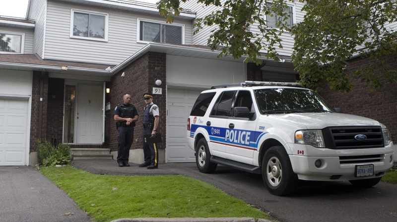 Police stand guard outside a home in the west end of Ottawa, Wednesday, Aug. 25, 2010. (Adrian Wyld / THE CANADIAN PRESS)
