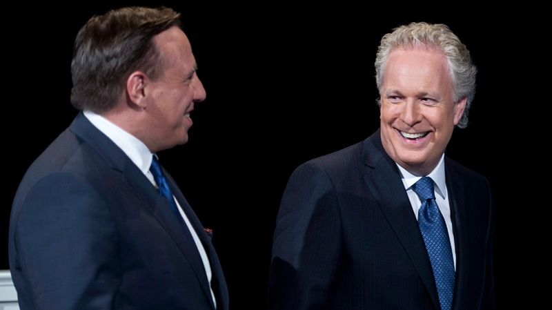 Quebec Premier Jean Charest chats with Coaltion Avenir Quebec leader Francois Legault while on the set prior to the leaders debate in Montreal Sunday, August 19, 2012. (Paul Chiasson / THE CANADIAN PRESS)