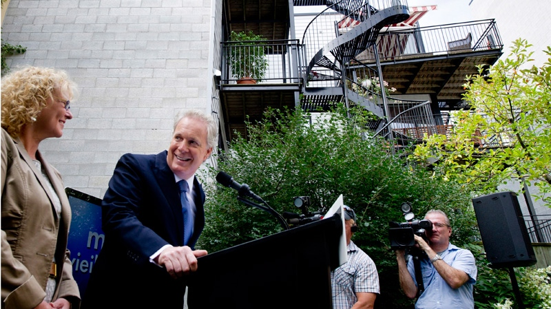 Quebec Premier Jean Charest, with candidate Marguerite Blais, responds to a question during a news conference in the backyard of a family home in Montreal Tuesday, August 21, 2012. (Paul Chiasson / THE CANADIAN PRESS)