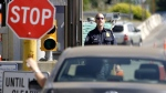 A U.S. Customs and Border Protection officer looks toward a car coming toward him at the border crossing between the U.S. and Canada, in Blaine, Wash. on Saturday, May 30, 2009. (Elaine Thompson/AP)