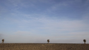 In this Thursday, Feb. 11, 2010 file photo, U.S. Marines patrol outside Marjah in Afghanistan's Helmand province. (AP Photo/David Guttenfelder, File)