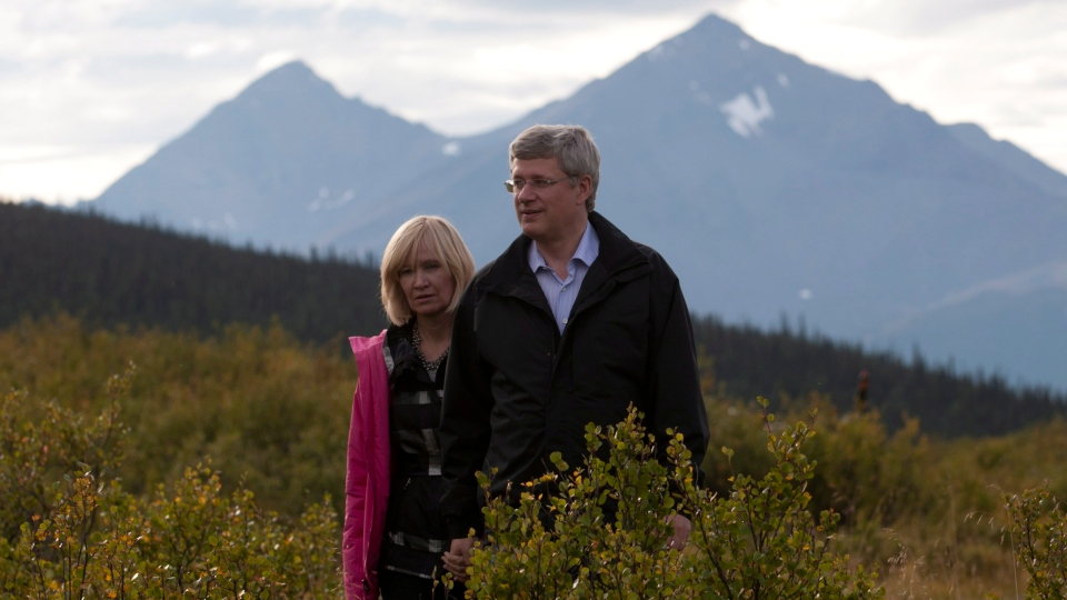 Prime Minister Stephen Harper and his wife Laureen walk through shrubs as they stand on the ground where a new national park will be located in Moose Pond, N.W.T., Tuesday, Aug. 21, 2012. (Adrian Wyld / THE CANADIAN PRESS)