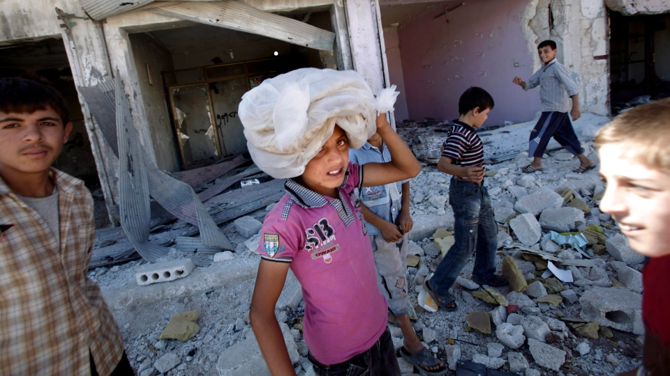 A Syrian boy carries carrying a bag of bread on his head while walking back to his home, in the city of Azaz, on the outskirts of Aleppo, Syria, Wednesday, Aug. 22, 2012. (AP / Muhammed Muheisen)