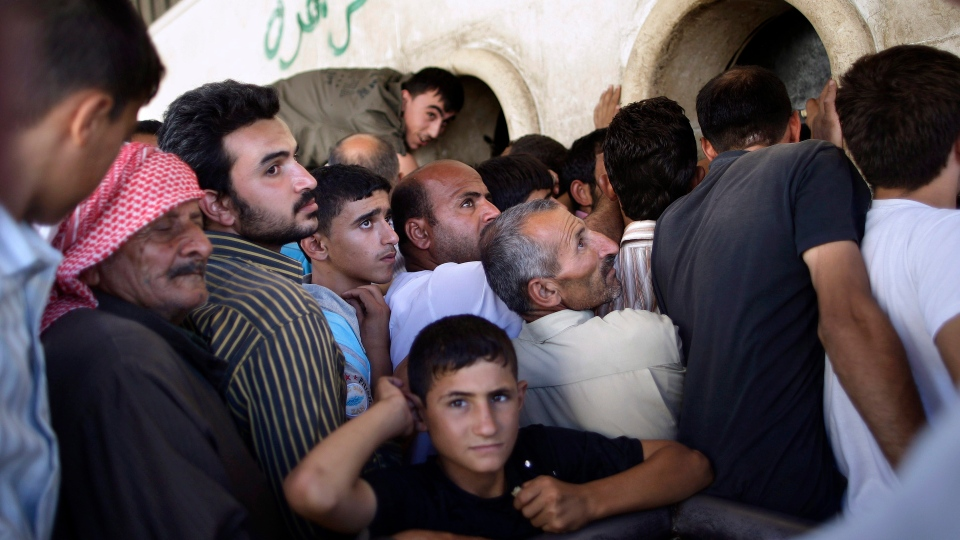 Syrians wait their turn to buy bread, outside a bakery shop in Kafar Hamra, on the outskirts of Aleppo, Syria, Wednesday, Aug. 22, 2012. (AP / Muhammed Muheisen)
