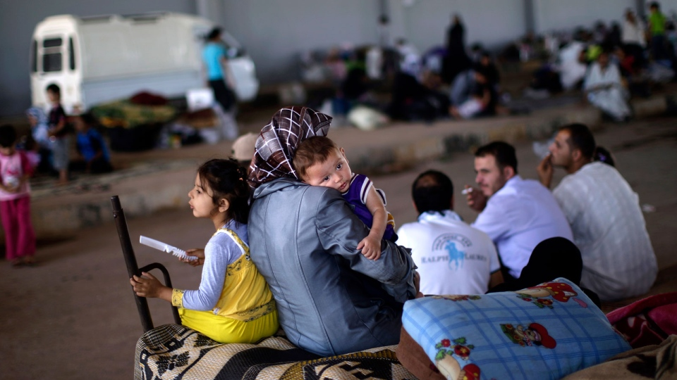 Syrians, who fled their homes due to fighting between the Syrian army and the rebels, take refuge at the Bab Al-Salameh border crossing, near Azaz, Syria, Thursday, Aug. 23, 2012. (AP / Muhammed Muheisen)