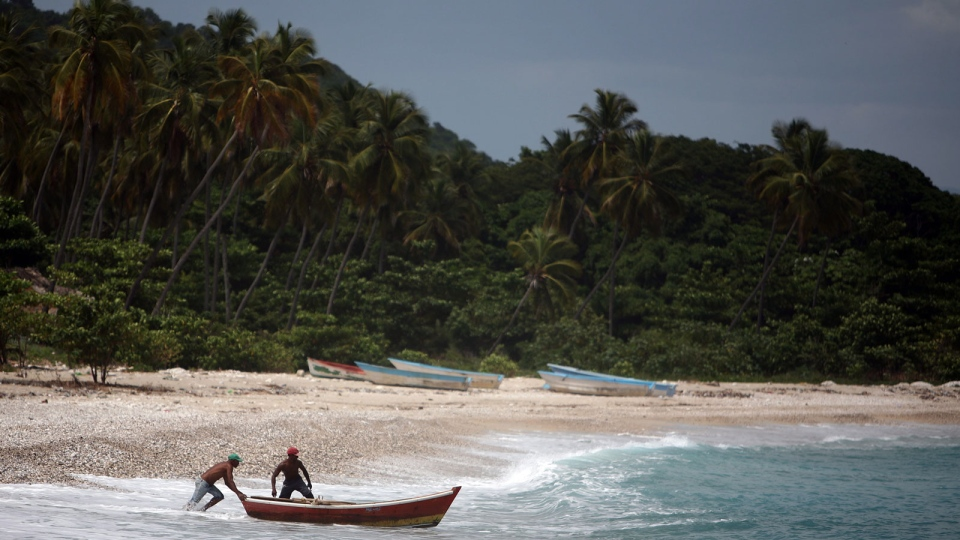 Fishermen launch their small wooden boat in Barahona, Dominican Republic, Thursday, Aug. 23, 2012.