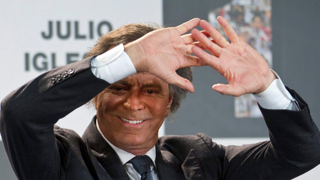 Spanish singer Julio Iglesias shields his eyes from the spotlights after receiving two awards in Mad