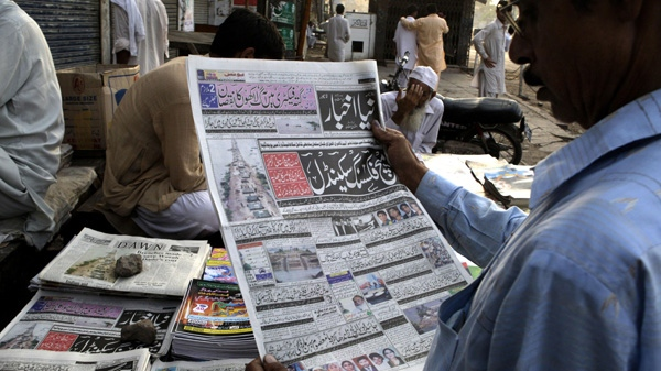 "A man reads an evening newspaper with a headline in Urdu reading, ""match-fixing scandal"", at a news stand in Lahore, Pakistan, Sunday, Aug. 29, 2010. (AP Photo/K.M. Chaudary)"