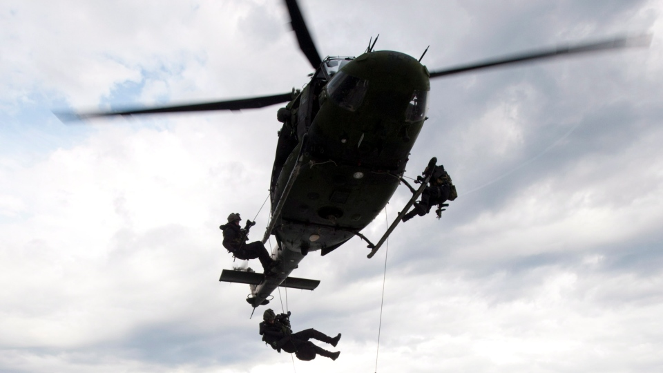 Members of Canadian Forces Special Operations JTF2 unit rappel from a helicopter as they storm a ship during Operation Nanook off the shores of Churchill, Man., Friday Aug. 24, 2012. (Adrian Wyld / THE CANADIAN PRESS)