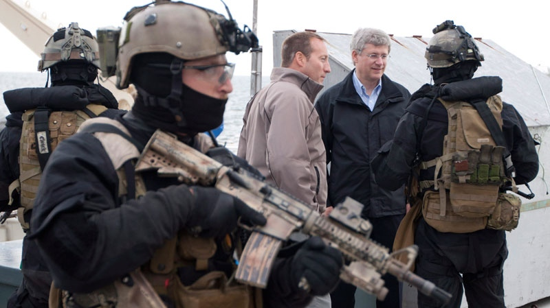 Prime Minister Stephen Harper and Minister of National Defence Peter MacKay speak with a member of the Canadian Forces Special Operations JTF2 unit after they stormed a ship during Operation Nanook off the shores of Churchill, Man. Friday, August 24, 2012. (Adrian Wyld / THE CANADIAN PRESS)