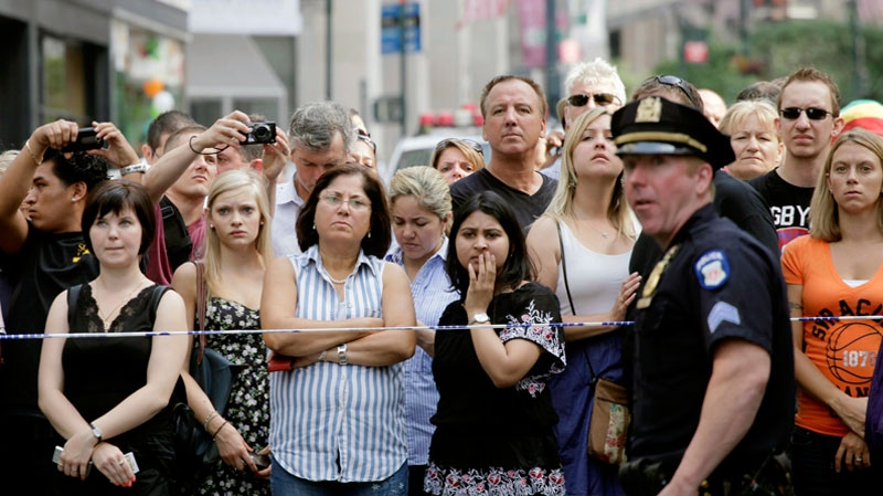 Bystanders and a police officer stand on Fifth Avenue to view the scene after a multiple shooting outside the Empire State Building in New York City, Friday, Aug. 24, 2012. (AP / Mark Lennihan)