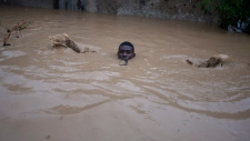 A man carrying a bottle in his mouth slips as he wades through a flooded street