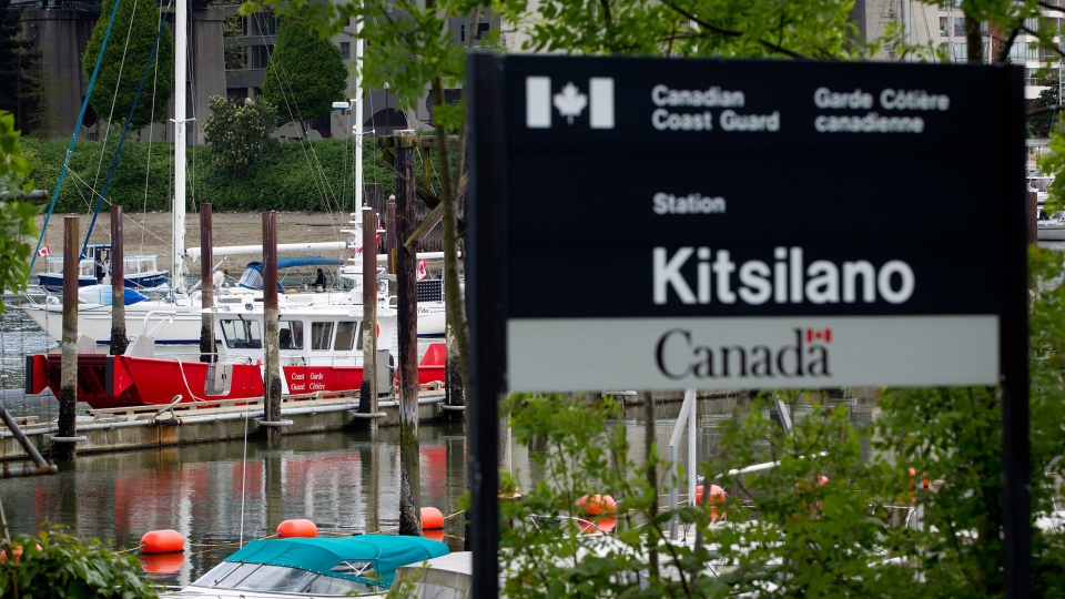 A sailboat and water taxi pass a Coast Guard vessel moored at the Coast Guard's Kitsilano Station in Vancouver, B.C., on Friday May 18, 2012. (Darryl Dyck/THE CANADIAN PRESS)